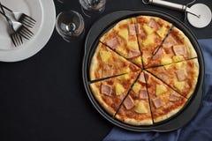 Σπιτικά φρούτα και κρέας της Χαβάης πιτσών στο σκοτεινό υπόβαθρο πλακών με το επιτραπέζιο σκεύος Στοκ εικόνες με δικαίωμα ελεύθερης χρήσης