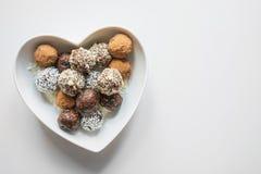 Σπιτικά φυσικά ενεργειακά δαγκώματα, vegan τρούφα σοκολάτας με το κακάο στο λευκό Υγιή τρόφιμα για τα παιδιά, υποκατάστατο γλυκών στοκ εικόνα