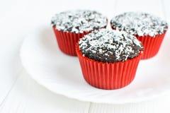 Σπιτικά cupcakes με το λούστρο και την καρύδα σοκολάτας Στοκ Φωτογραφία