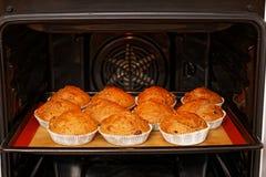 Σπιτικά cupcakes στη φόρμα εγγράφου στο φούρνο στοκ φωτογραφία με δικαίωμα ελεύθερης χρήσης