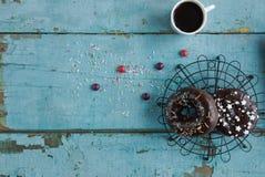 σπιτικά donuts σε χαρτί και το μαύρο καφέ σε ένα άσπρο φλυτζάνι Στοκ φωτογραφίες με δικαίωμα ελεύθερης χρήσης