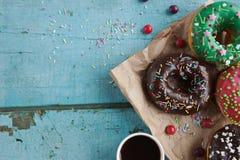 σπιτικά donuts σε χαρτί και το μαύρο καφέ σε ένα άσπρο φλυτζάνι Στοκ Εικόνες