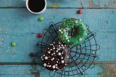 σπιτικά donuts σε χαρτί και το μαύρο καφέ σε ένα άσπρο φλυτζάνι Στοκ Φωτογραφίες