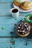 σπιτικά donuts σε χαρτί και το μαύρο καφέ σε ένα άσπρο φλυτζάνι Στοκ Εικόνα