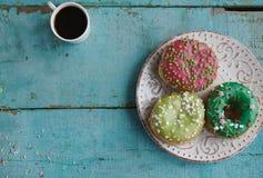 σπιτικά donuts σε χαρτί και το μαύρο καφέ σε ένα άσπρο φλυτζάνι Στοκ φωτογραφία με δικαίωμα ελεύθερης χρήσης