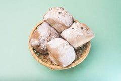 Σπιτικά muffins με τις σταφίδες και η κονιοποιημένη ζάχαρη σε ένα ψάθινο καλάθι ενάντια σε μια ελαφριά μέντα χρωματίζουν Στοκ εικόνα με δικαίωμα ελεύθερης χρήσης