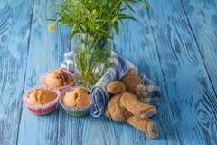 Σπιτικά muffins στην μπλε πετσέτα στον μπλε ξύλινο πίνακα Στοκ Εικόνες