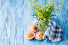 Σπιτικά muffins στην μπλε πετσέτα στον μπλε ξύλινο πίνακα Στοκ εικόνα με δικαίωμα ελεύθερης χρήσης