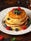 Σπιτικές αμερικανικές τηγανίτες με το φρέσκα βακκίνιο, τα σμέουρα και το μέλι Υγιές αγροτικό ύφος προγευμάτων πρωινού στοκ εικόνες με δικαίωμα ελεύθερης χρήσης