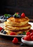 Σπιτικές αμερικανικές τηγανίτες με το φρέσκα βακκίνιο, τα σμέουρα και το μέλι Υγιές αγροτικό ύφος προγευμάτων πρωινού στοκ εικόνες