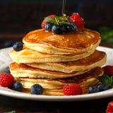 Σπιτικές αμερικανικές τηγανίτες με το φρέσκα βακκίνιο, τα σμέουρα και το μέλι Υγιές αγροτικό ύφος προγευμάτων πρωινού στοκ φωτογραφία με δικαίωμα ελεύθερης χρήσης