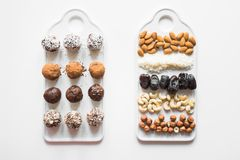 Σπιτικές ενεργειακές σφαίρες με το κακάο και καρύδια στο λευκό Υγιή τρόφιμα για τα παιδιά, υποκατάστατο γλυκών στοκ εικόνες με δικαίωμα ελεύθερης χρήσης