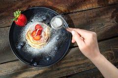 Σπιτικές τηγανίτες με τις φράουλες, τα βακκίνια και την κονιοποιημένη ζάχαρη γλυκό προγευμάτων στοκ εικόνες