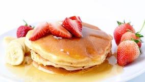Σπιτικές τηγανίτες με τις φρέσκες φράουλες και την μπανάνα φετών και μέλι στο άσπρο πιάτο, υγιές πρόγευμα απόθεμα βίντεο