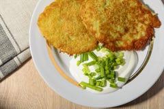 Σπιτικές τηγανισμένες τηγανίτες πατατών με την ξινή κρέμα και τα πράσινα κρεμμύδια Στοκ εικόνα με δικαίωμα ελεύθερης χρήσης
