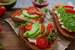 σπιτικές φρυγανιές αβοκάντο στο ψωμί σίκαλης, τις ντομάτες, τα scallions, το τυρί πιπεριών και κρέμας Στοκ φωτογραφία με δικαίωμα ελεύθερης χρήσης