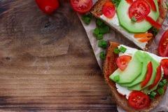 σπιτικές φρυγανιές αβοκάντο στο ψωμί σίκαλης, τις ντομάτες, τα scallions, το τυρί πιπεριών και κρέμας Στοκ Φωτογραφία