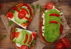 σπιτικές φρυγανιές αβοκάντο στο ψωμί σίκαλης, τις ντομάτες, τα scallions, το τυρί πιπεριών και κρέμας Στοκ Εικόνες