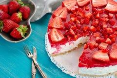 Σπιτική κρεμώδης πίτα κέικ επιδορπίων των κόκκινων νωπών καρπών φραουλών στο μπλε ξύλινο υπόβαθρο Στοκ Εικόνα