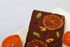 Σπιτική μαύρη σοκολάτα Διακοσμημένος με τις φέτες του ξηρών πορτοκαλιού, των φραουλών, των κερασιών και των φυστικιών στοκ φωτογραφίες