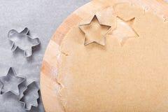 Σπιτική οργανική βουτύρου ζύμη μπισκότων ζάχαρης έννοιας ψησίματος στη στρογγυλή ξύλινη διάφορη μορφή κοπτών πινάκων και μπισκότω στοκ εικόνα