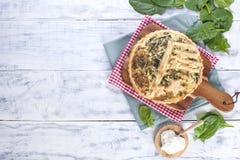 Σπιτική πίτα με το σπανάκι και το τυρί, σε ένα άσπρο ξύλινο υπόβαθρο εξυπηρέτηση της πίτας στοκ φωτογραφίες με δικαίωμα ελεύθερης χρήσης