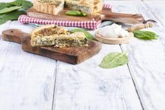 Σπιτική πίτα με το σπανάκι και το τυρί, σε ένα άσπρο ξύλινο υπόβαθρο εξυπηρέτηση της πίτας Στοκ Εικόνα