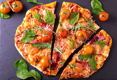 Σπιτική πίτσα με το μπέϊκον, τις ντομάτες, το σπανάκι, το arugula και το τυρί Στοκ Φωτογραφίες