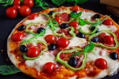 Σπιτική πίτσα με το σαλάμι, τις μαύρους ελιές και το βασιλικό Στοκ Εικόνα