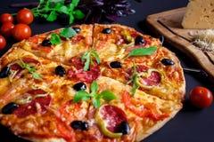 Σπιτική πίτσα με το σαλάμι, τις μαύρους ελιές και το βασιλικό Στοκ Εικόνες