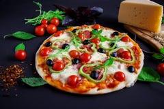 Σπιτική πίτσα με το σαλάμι, τις μαύρους ελιές και το βασιλικό Στοκ Φωτογραφίες