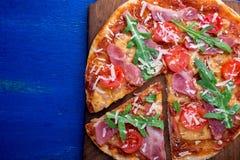 Σπιτική πίτσα με το prosciutto, ντομάτα, arugula στο ξύλινο μπλε υπόβαθρο πινάκων Τοπ όψη Στοκ Εικόνα