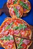 Σπιτική πίτσα με το prosciutto, ντομάτα, arugula στο ξύλινο μπλε υπόβαθρο πινάκων Τοπ όψη Στοκ Εικόνες