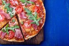 Σπιτική πίτσα με το prosciutto, ντομάτα, arugula στο ξύλινο μπλε υπόβαθρο πινάκων Τοπ όψη Στοκ εικόνες με δικαίωμα ελεύθερης χρήσης
