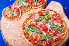 Σπιτική πίτσα με το prosciutto, ντομάτα, arugula στο ξύλινο μπλε υπόβαθρο πινάκων Τοπ όψη Στοκ φωτογραφίες με δικαίωμα ελεύθερης χρήσης