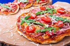 Σπιτική πίτσα με το prosciutto, ντομάτα, arugula στο ξύλινο μπλε υπόβαθρο πινάκων Στοκ Εικόνα