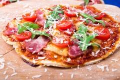 Σπιτική πίτσα με το prosciutto, ντομάτα, arugula στο ξύλινο μπλε υπόβαθρο πινάκων Στοκ φωτογραφίες με δικαίωμα ελεύθερης χρήσης
