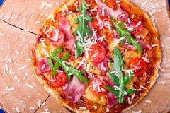 Σπιτική πίτσα με το prosciutto, ντομάτα, arugula στο ξύλινο μπλε υπόβαθρο πινάκων Τοπ όψη Στοκ Φωτογραφίες