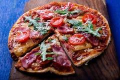 Σπιτική πίτσα με το prosciutto, ντομάτα, arugula στο ξύλινο μπλε υπόβαθρο πινάκων Στοκ φωτογραφία με δικαίωμα ελεύθερης χρήσης