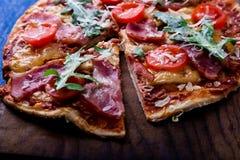 Σπιτική πίτσα με το prosciutto, ντομάτα, arugula στο ξύλινο μπλε υπόβαθρο πινάκων Στοκ Φωτογραφία