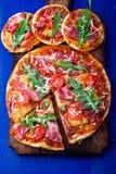 Σπιτική πίτσα με το prosciutto, ντομάτα, arugula στο ξύλινο μπλε υπόβαθρο πινάκων Τοπ όψη Στοκ φωτογραφία με δικαίωμα ελεύθερης χρήσης