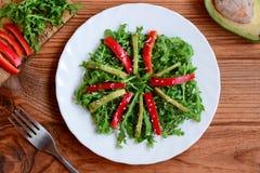 Σπιτική σαλάτα αβοκάντο, arugula και πιπεριών Πράσινη σαλάτα arugula και αβοκάντο με το φρέσκο πιπέρι και σουσάμι σε ένα άσπρο πι Στοκ Φωτογραφία