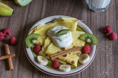 Σπιτική τηγανίτα με τη στάρπη βανίλιας, τα σμέουρα, τα κομμάτια ακτινίδιων και μπανανών που ψεκάζονται με το κακάο Στοκ εικόνες με δικαίωμα ελεύθερης χρήσης