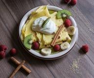 Σπιτική τηγανίτα με τη στάρπη βανίλιας, τα σμέουρα, τα κομμάτια ακτινίδιων και μπανανών που ψεκάζονται με το κακάο Στοκ φωτογραφίες με δικαίωμα ελεύθερης χρήσης