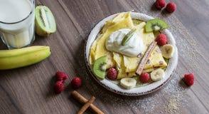 Σπιτική τηγανίτα με τη στάρπη βανίλιας, τα σμέουρα, τα κομμάτια ακτινίδιων και μπανανών που ψεκάζονται με το κακάο Στοκ Φωτογραφία