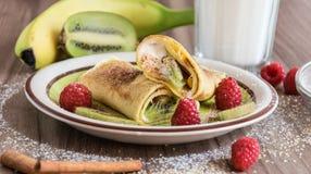 Σπιτική τηγανίτα με τη στάρπη βανίλιας, τα σμέουρα, τα κομμάτια ακτινίδιων και μπανανών που ψεκάζονται με το κακάο Στοκ Εικόνες