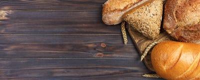 Σπιτική φραντζόλα του ψωμιού σίτου που ψήνεται στο ξύλινο υπόβαθρο έμβλημα για τη διαφήμιση και το σχέδιο, τοπ άποψη promo με το  στοκ εικόνες