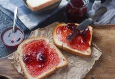 Σπιτική φρυγανιά με τη μαρμελάδα φραουλών στον ξύλινο πίνακα, εύγευστο πρόγευμα Στοκ Εικόνα