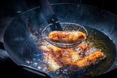 Σπιτικοί ρόλοι άνοιξη που τηγανίζουν στο καυτό πετρέλαιο στο μαύρο τηγάνι στοκ εικόνες