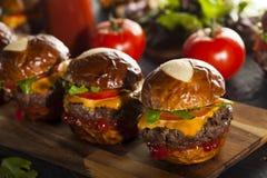 Σπιτικοί Cheeseburger ολισθαίνοντες ρυθμιστές με το μαρούλι Στοκ Φωτογραφίες